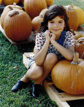 Photograph of girl with pumpkins